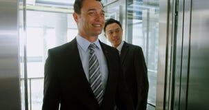 Hombres de negocios el salir del elevador en la oficina 4k almacen de video