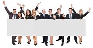 Hombres de negocios emocionados que presentan la bandera vacía Fotografía de archivo libre de regalías