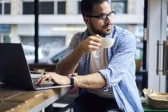 Hombres de negocios en camisa azul usando la conexión inalámbrica libre a Internet en café Fotos de archivo libres de regalías
