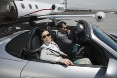 Hombres de negocios en coche en el campo de aviación Fotos de archivo libres de regalías