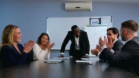 Hombres de negocios en desgaste formal que aplauden mientras que se sienta junto en la tabla almacen de video