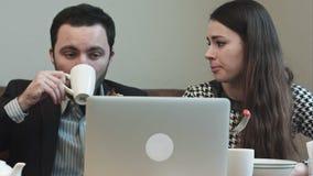 Hombres de negocios en el almuerzo que mira en la pantalla del ordenador portátil y que discute mientras que come y bebe almacen de video