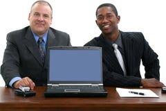 Hombres de negocios en el escritorio con la computadora portátil Imagen de archivo