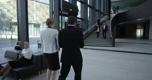 Hombres de negocios en el pasillo del edificio de oficinas metrajes