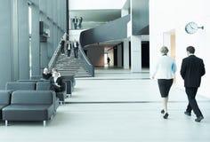 Hombres de negocios en el pasillo del edificio de oficinas Foto de archivo libre de regalías