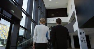 Hombres de negocios en el pasillo del edificio de oficinas almacen de metraje de vídeo