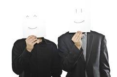 Hombres de negocios en juegos con las hojas de papel, emoticons Imágenes de archivo libres de regalías