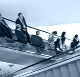 Hombres de negocios en la escalera móvil Fotografía de archivo