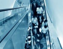 Hombres de negocios en la escalera móvil Fotos de archivo libres de regalías