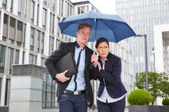 Hombres de negocios en la lluvia debajo del paraguas en la ciudad Fotos de archivo