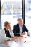 Hombres de negocios en la mesa de reuniones Imagen de archivo libre de regalías
