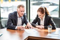 Hombres de negocios en la mesa de reuniones imagen de archivo