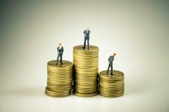 Hombres de negocios en la pila de monedas La inclinación y la explotación agrícola asiáticas del hombre de negocios de la competi Imagen de archivo libre de regalías