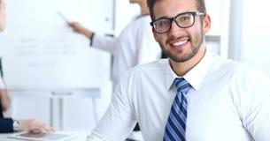 Hombres de negocios en la reunión en oficina Céntrese en los vidrios que llevan sonrientes alegres del hombre barbudo Conferencia fotografía de archivo libre de regalías