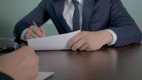 Hombres de negocios en la tabla para firmar el contrato y para sellar el trato con un apret?n de manos almacen de metraje de vídeo