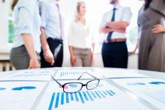 Hombres de negocios en oficina con datos financieros Imagen de archivo libre de regalías