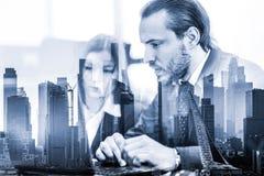 Hombres de negocios en oficina moderna contra reflexiones de la ventana de los edificios y de los rascacielos de New York City Ma foto de archivo
