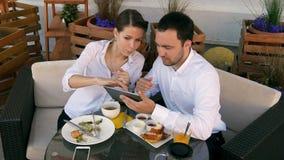 Hombres de negocios en un restaurante usando un dispositivo de la tableta almacen de metraje de vídeo
