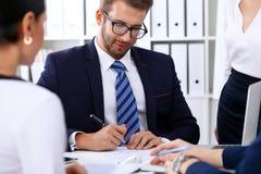 Hombres de negocios en una reunión en la oficina Céntrese en hombre del jefe mientras que firma el contrato o los papeles financi fotografía de archivo libre de regalías