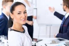 Hombres de negocios en una reunión en la oficina Foco en mujer del jefe Foto de archivo libre de regalías