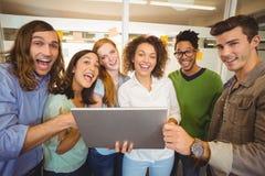 Hombres de negocios felices con el ordenador portátil en meting el sitio Fotos de archivo libres de regalías