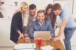 Hombres de negocios felices del equipo así como el ordenador portátil en oficina Imágenes de archivo libres de regalías