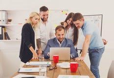 Hombres de negocios felices del equipo así como el ordenador portátil en oficina Imagen de archivo libre de regalías