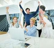 Hombres de negocios felices que animan en oficina fotos de archivo
