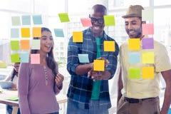 Hombres de negocios felices que discuten sobre notas adhesivas Imágenes de archivo libres de regalías