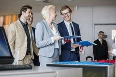 Hombres de negocios felices que hablan mientras que ficheros de tenencia en el contador de la recepción en centro de convenio foto de archivo