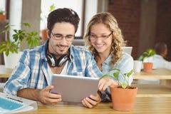 Hombres de negocios felices que miran la tableta digital en oficina creativa Fotografía de archivo