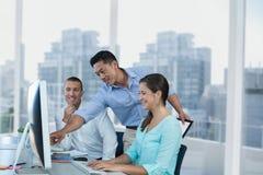 Hombres de negocios felices que miran un ordenador contra fondo de la ciudad fotos de archivo libres de regalías