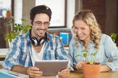 Hombres de negocios felices que ríen mientras que mira la tableta digital la oficina Imágenes de archivo libres de regalías