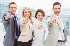 Hombres de negocios felices que señalan en usted en oficina Imágenes de archivo libres de regalías