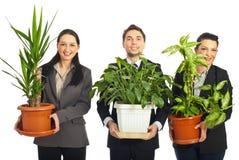 Hombres de negocios felices que sostienen los floreros con las plantas Imágenes de archivo libres de regalías