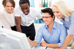 Hombres de negocios felices recolectados alrededor del ordenador fotografía de archivo