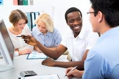 Hombres de negocios felices recolectados alrededor del ordenador portátil imagen de archivo libre de regalías