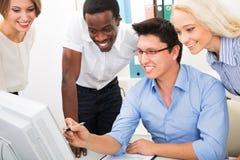 Hombres de negocios felices recolectados alrededor del ordenador portátil Imágenes de archivo libres de regalías
