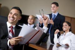 Hombres de negocios hispánicos en la sonrisa de la sala de reunión Imágenes de archivo libres de regalías