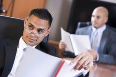 Hombres de negocios hispánicos en informe de repaso de la sala de reunión Fotografía de archivo