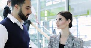 Hombres de negocios Hombre y mujer que hablan en el trabajo en oficina metrajes
