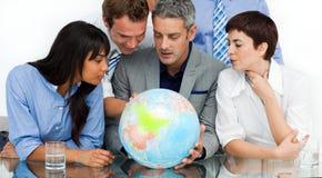 Hombres de negocios internacionales que miran un globo Foto de archivo