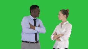Hombres de negocios internacionales que se colocan con las armas dobladas en una pantalla verde, llave de la croma almacen de video