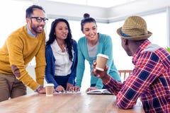 Hombres de negocios jovenes alegres que discuten en la oficina creativa Foto de archivo libre de regalías