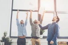 Hombres de negocios jovenes alegres que triunfan y que lanzan los papeles en negocio de la oficina imagen de archivo