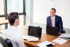 Hombres de negocios jovenes americanos que obran recíprocamente y que hablan trabajo en equipo en la reunión en oficina Imagen de archivo