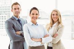 Hombres de negocios jovenes con los brazos cruzados en oficina imagen de archivo libre de regalías