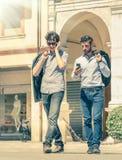 Hombres de negocios jovenes en la plaza principal de la ciudad con smartphone Foto de archivo libre de regalías