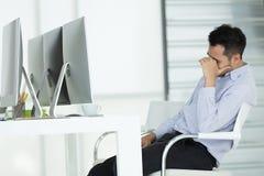 Hombres de negocios jovenes en la tensión Siéntese delante de compu moderno de la oficina imagen de archivo