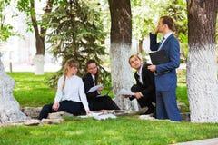 Hombres de negocios jovenes en un parque Foto de archivo libre de regalías